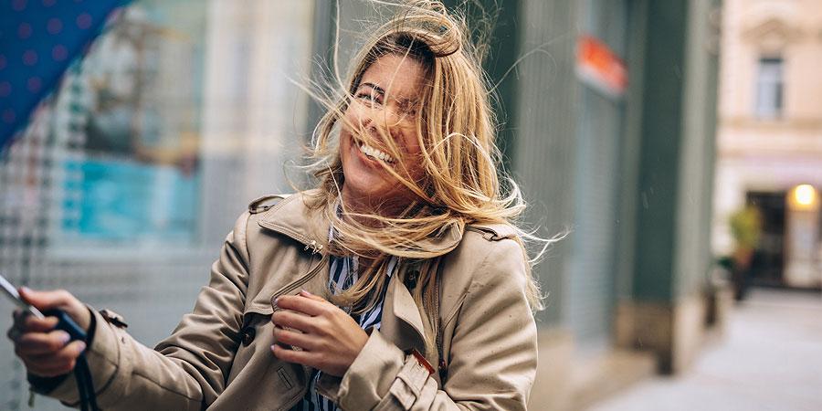 Frau im Wind mit zerzausten Haaren und Regenschirm, aber fröhlich