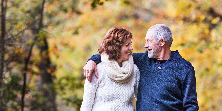 Mann und Frau gehen Arm in Arm in Herbstlandschaft spazieren