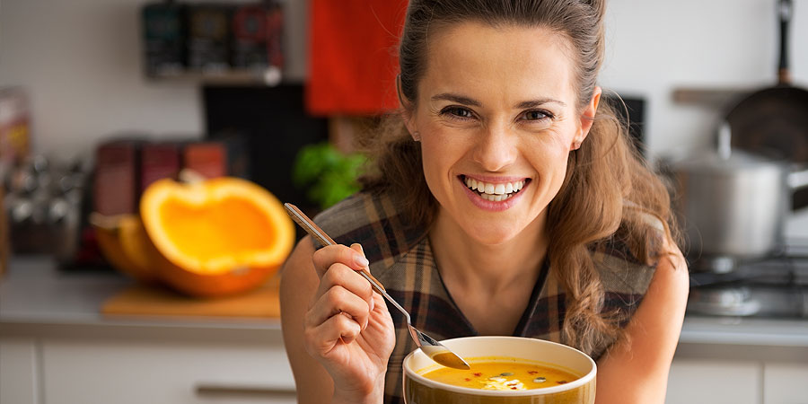 Frau in Küche mit Kürbissuppe