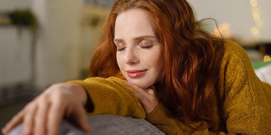 frau relaxt mit geschlossenen augen auf sofa