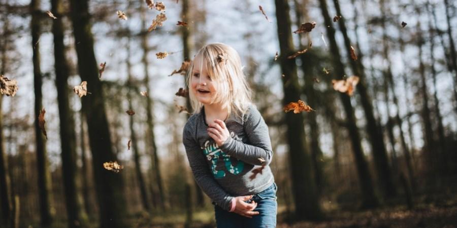 Mädchen spielt mit Herbstlaub