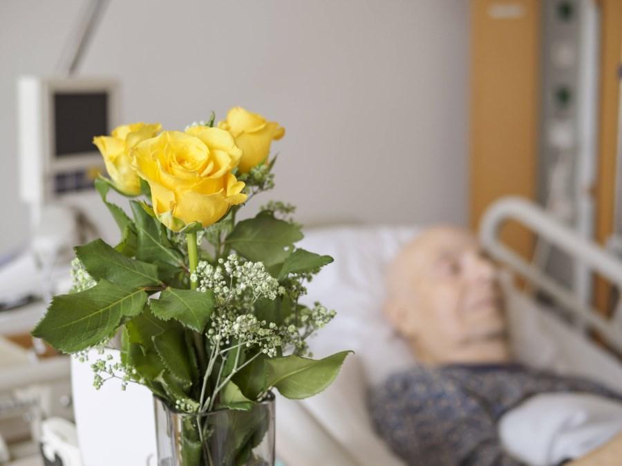alter Mann im Krankhausbett, vor ihm steht Strauß mit gelben Rosen
