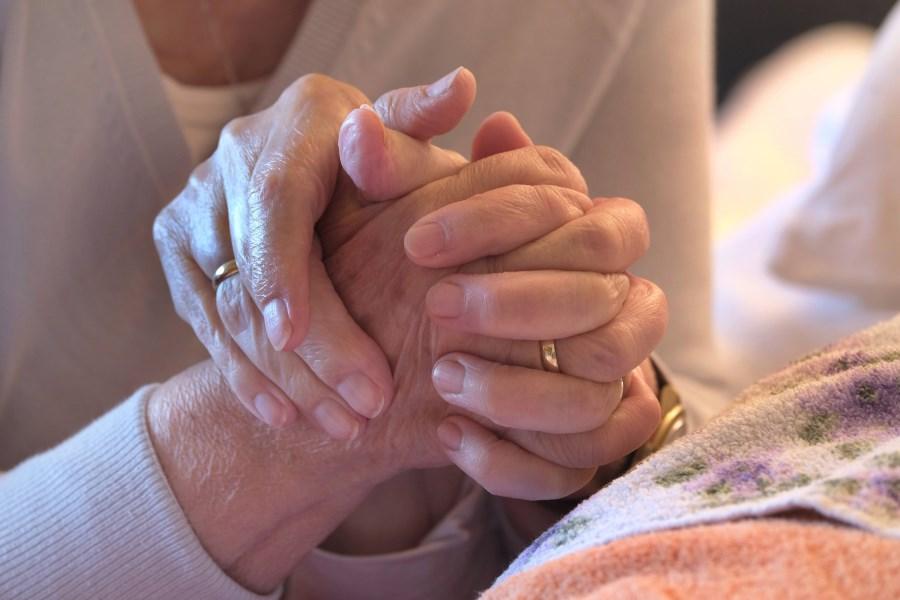 hände älterer frau halten hand pflegebedürftigen mannes