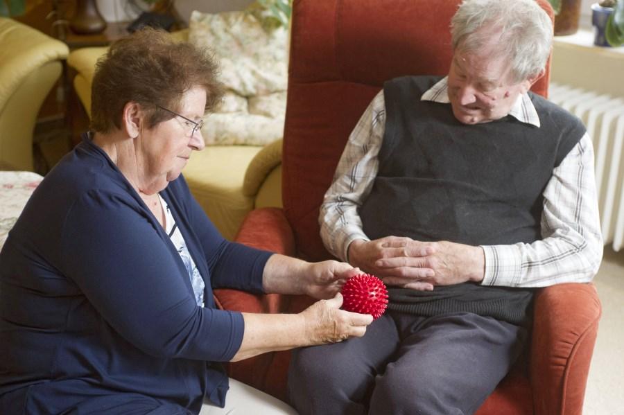 ältere Frau spielt mit älterem demenzkranken mann