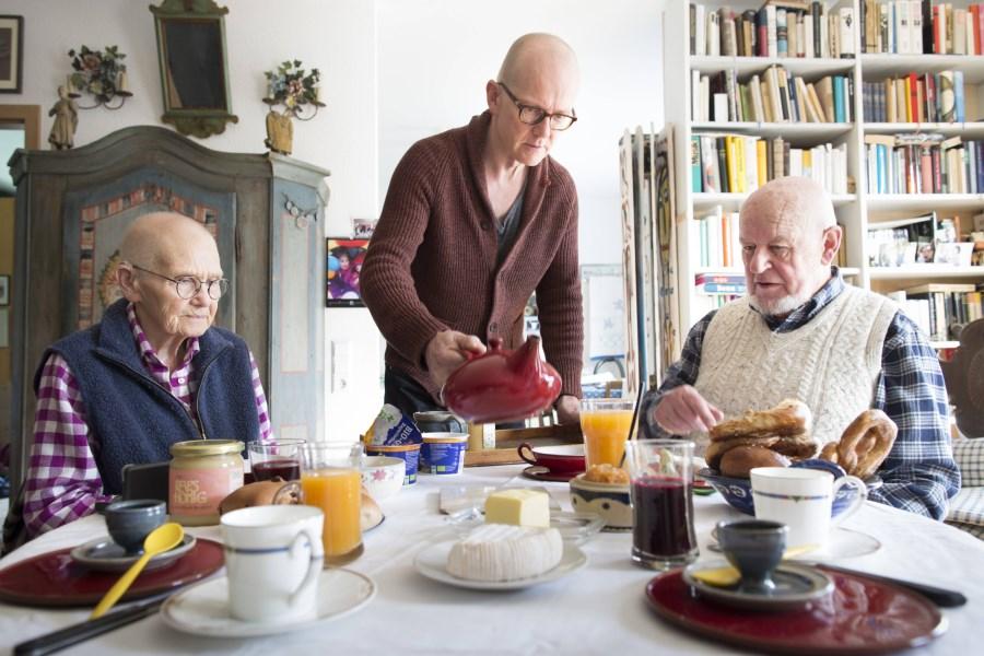 mann bedient pflegebedürftige eltern am tisch