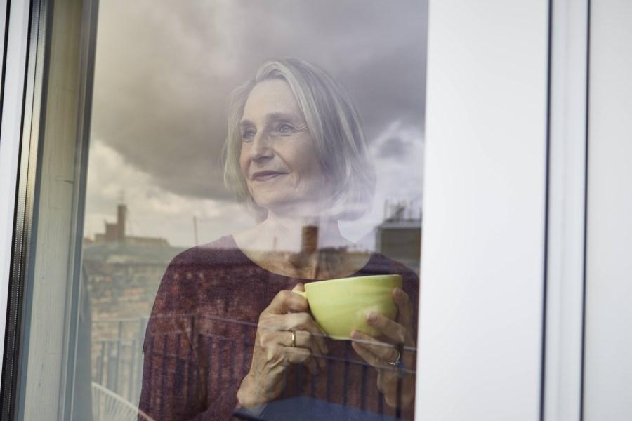erwachsene frau blickt aus fenster mit teetasse