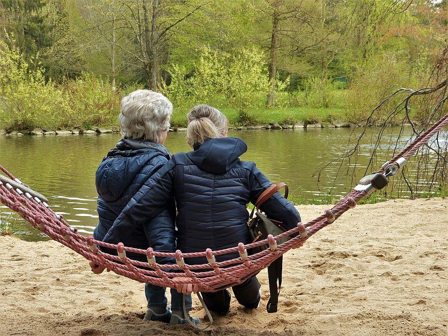 Eine ältere und eine jüngere Frauen sitzen mit dem Rücken zum Betrachter auf einer Hängematte an einem See