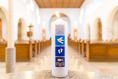 Taufkerze steht in einer Kirche