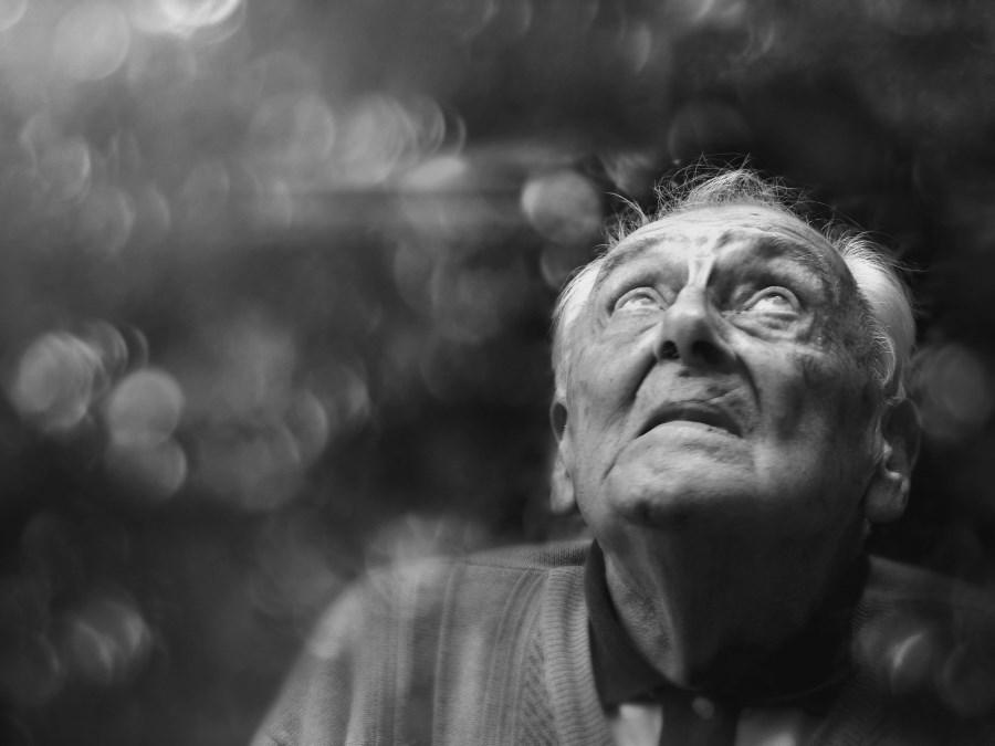 schwarz-weiß älterer Mann schaut verloren in den Himmel