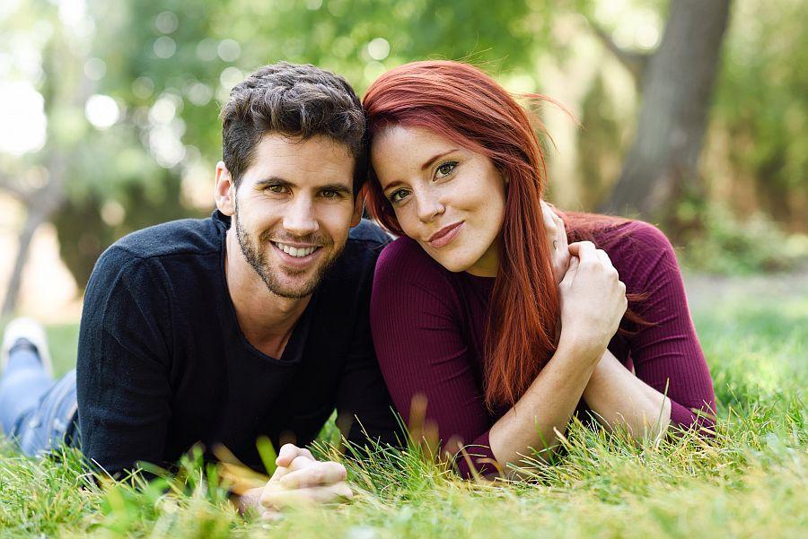 Junge Frau und junger Mann liegen lächelnd auf einer Wiese