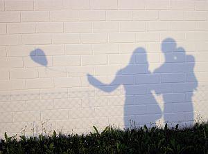 Schattenriss an einer Mauer: Eltern mit Baby und Luftballon
