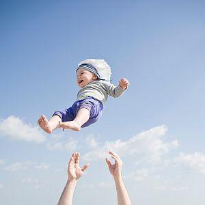 Lachendes Baby fliegt in der Luft, unter ihm zwei Hände