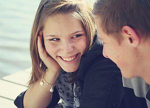 Junge Frau und junger Mann lächeln sich an