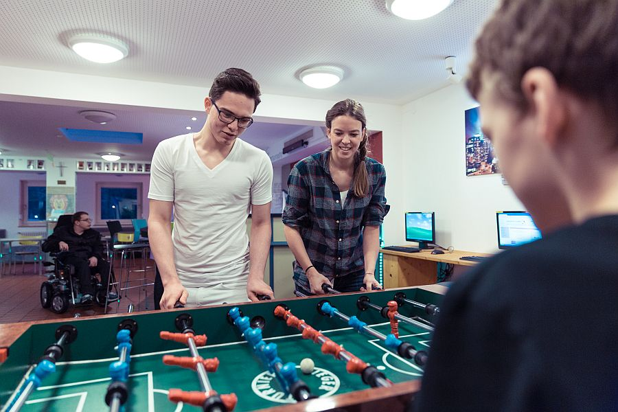 Junge Frau spielt mit zwei Jugendlichen am Tischkicker