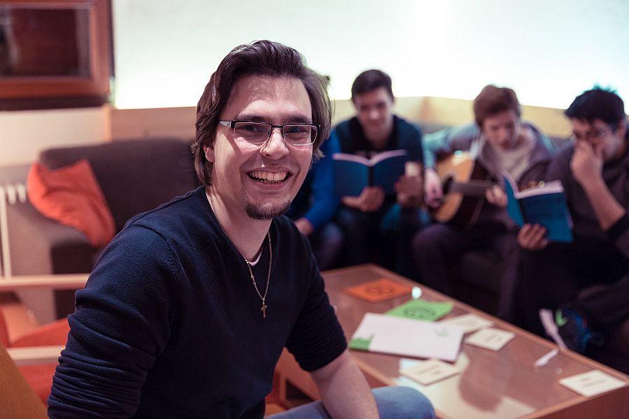 Junger Mann lacht, im Hintergrund Jugendliche mit Liederbüchern und Gitarre