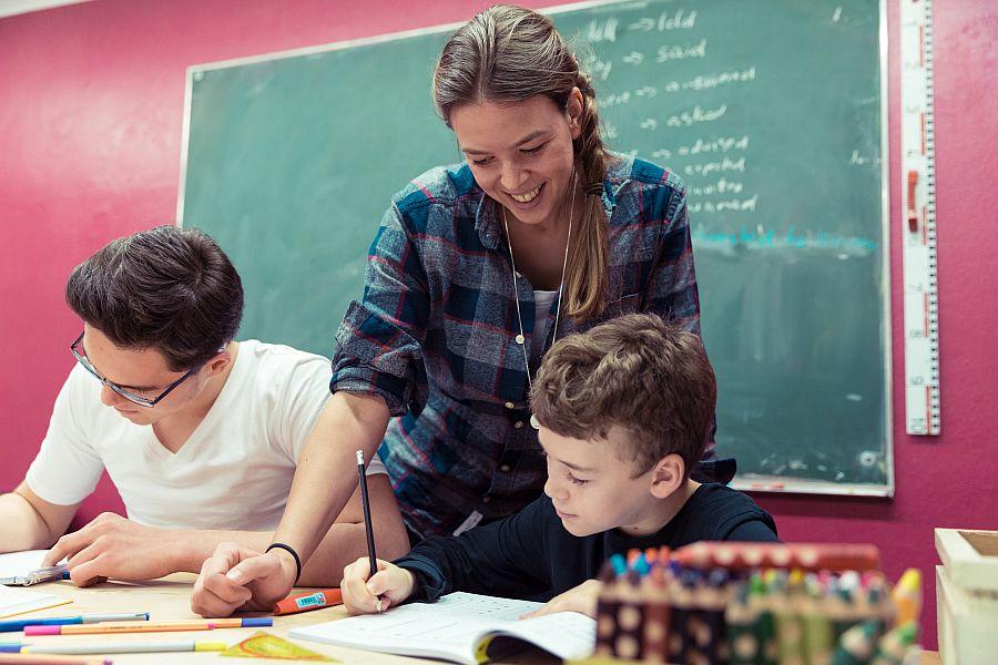 Junge Frau hilft zwei Jugendlichen, die an Schulbank sitzen und schreiben