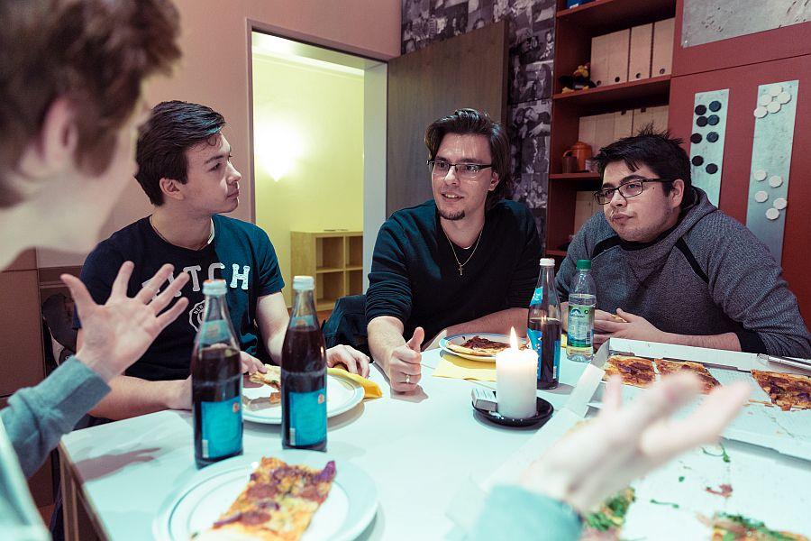 Junger Mann mit Jugendlichen im Gespräch beim Pizzaessen