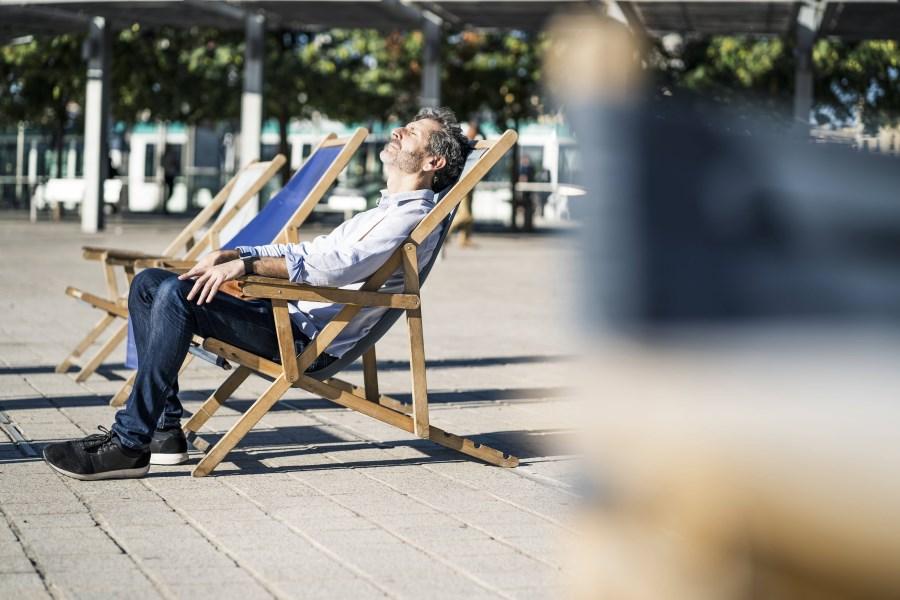Mann genießt Sonne in Liegestuhl