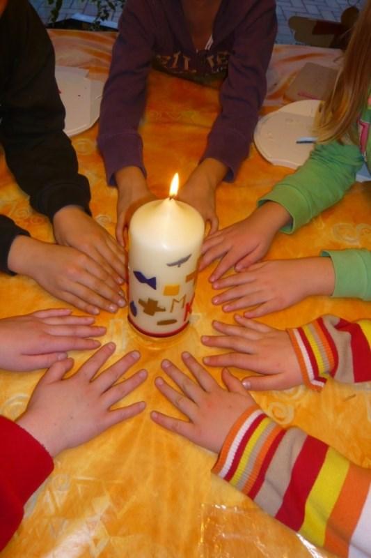 Erstkommunionkerze und Kinderhände