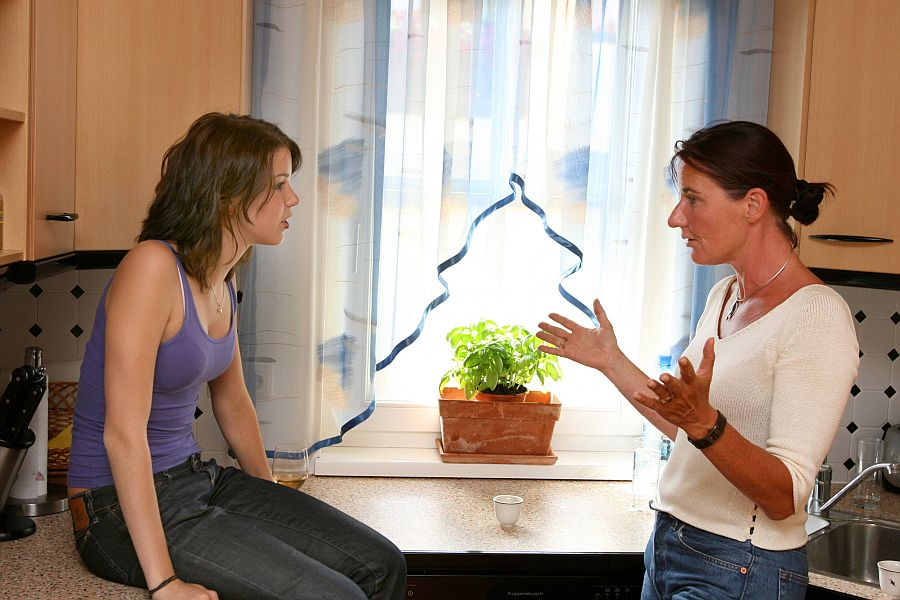 Mutter und jugendliche Tochter diskutieren in der Küche