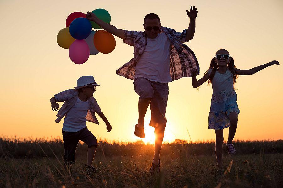 Vater mit Luftballons und zwei Kinder hüpfen fröhlich im Sonnenuntergang durch die Natur