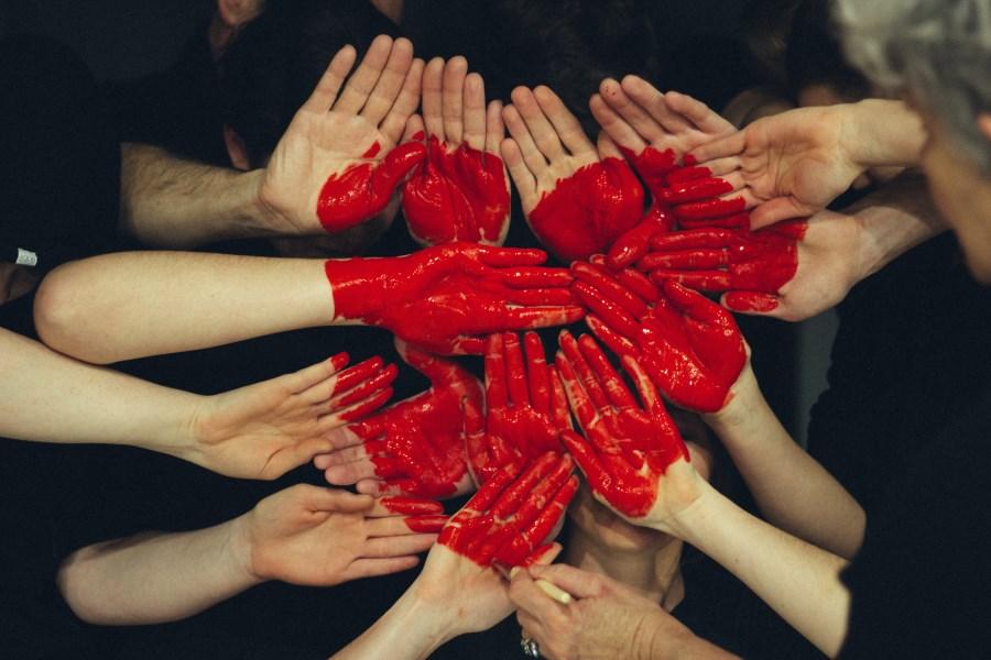 viele Hände bilden ein rotes Herz