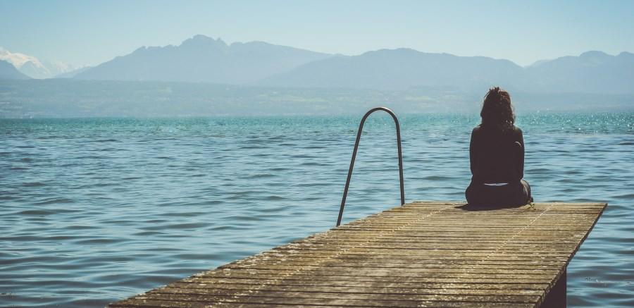 Frau sitzt an Steg am See