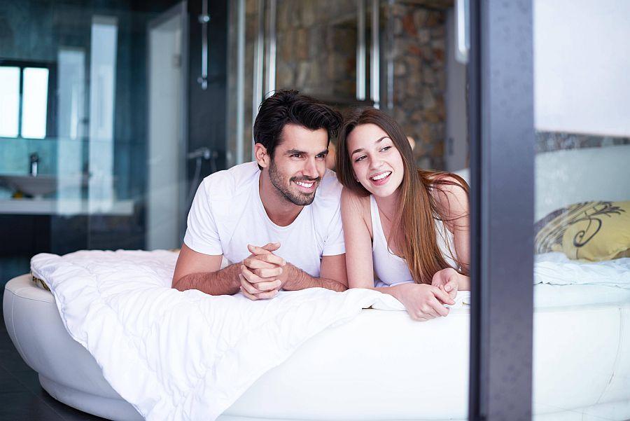 Glückliches Paar liegt im Schlafanzug auf Bett