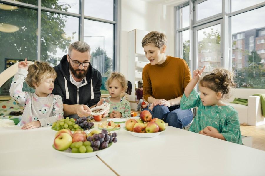 Erzieher und Erzieherin bereiten in der Kita mit Kindern frischen Obstteller vor