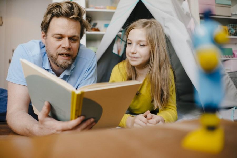 Vater liest mit Tochter ein Buch