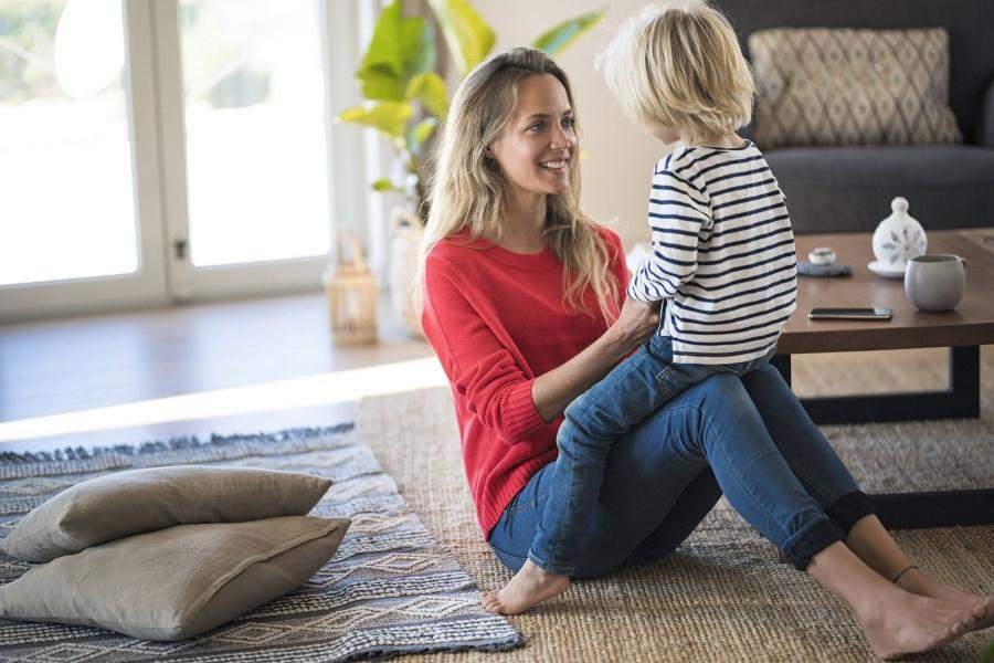 Mutter mit Kind auf den Knien im Wohnzimmer