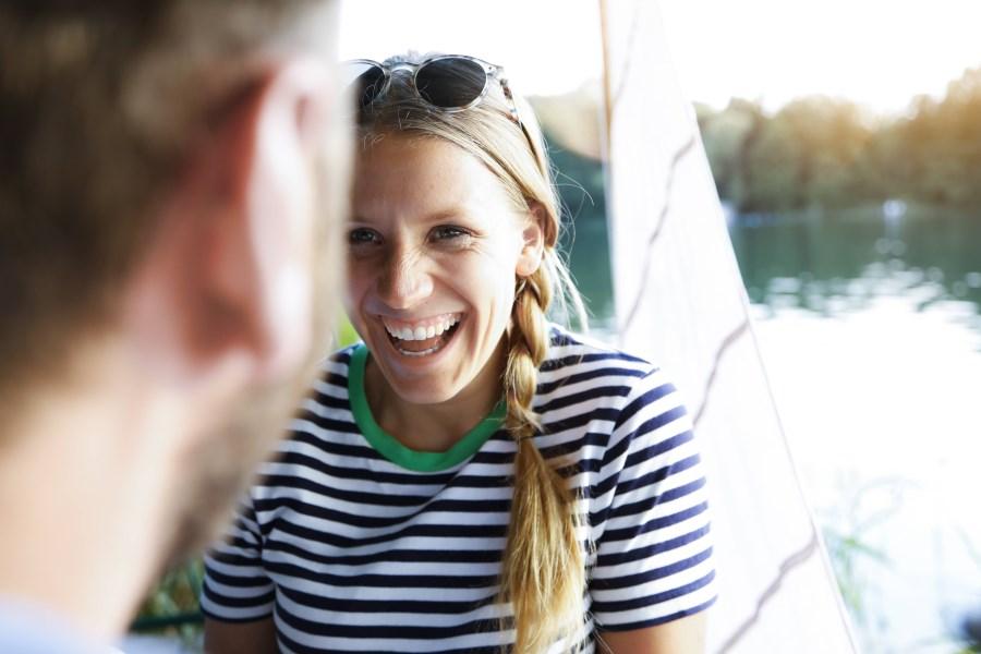 freundlich lachende Frau im Gespräch mit Mann