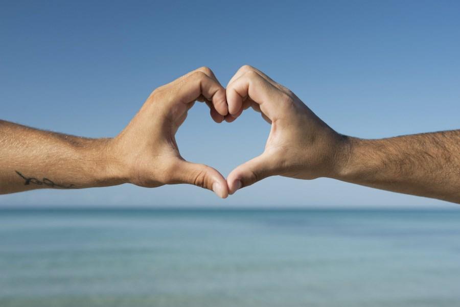 Hände von Mann und Frau bilden ein Herz vor Meer und Strand