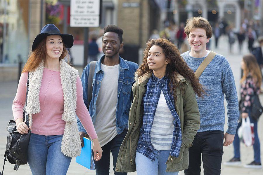 Jugendliche laufen lachend auf einer städtischen Straße