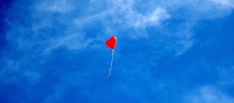 roter Herzballon fliegt in blauen Himmel_schmal
