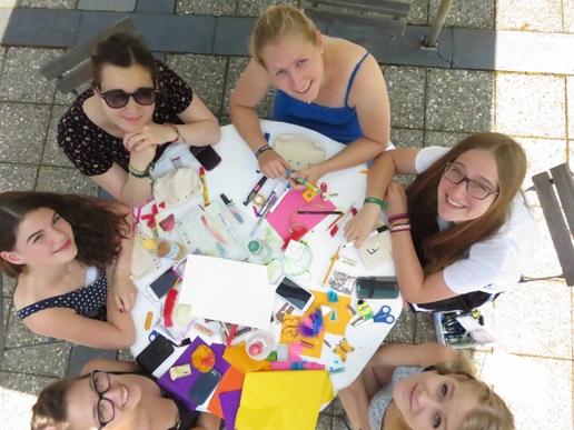 Vogelperspektive junge Frauen sitzen an buntem Tisch