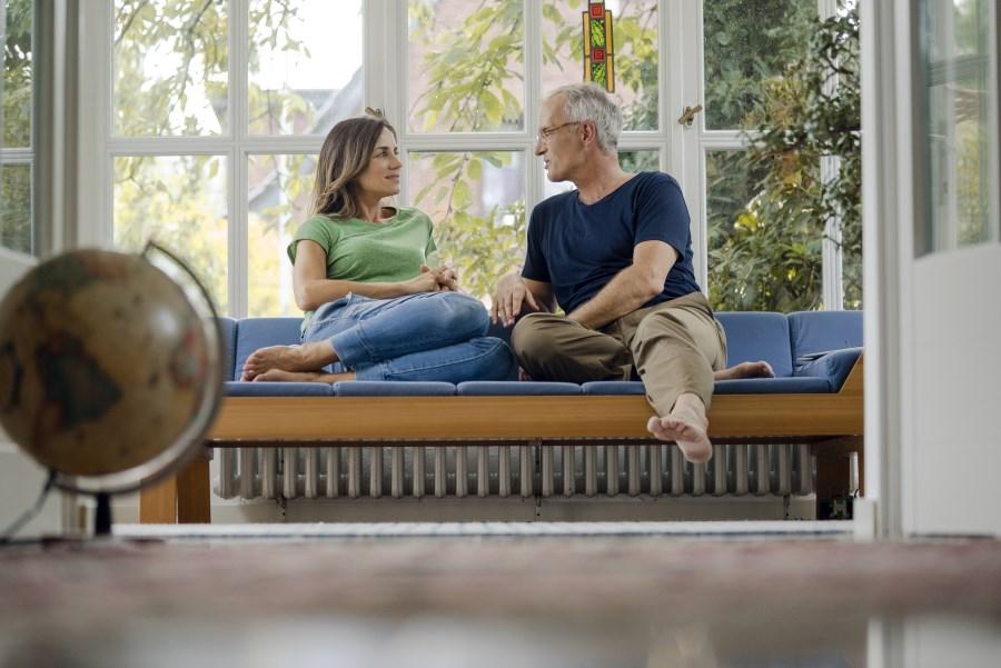 Paar sitzt auf Sofa am Fenster und unterhält sich