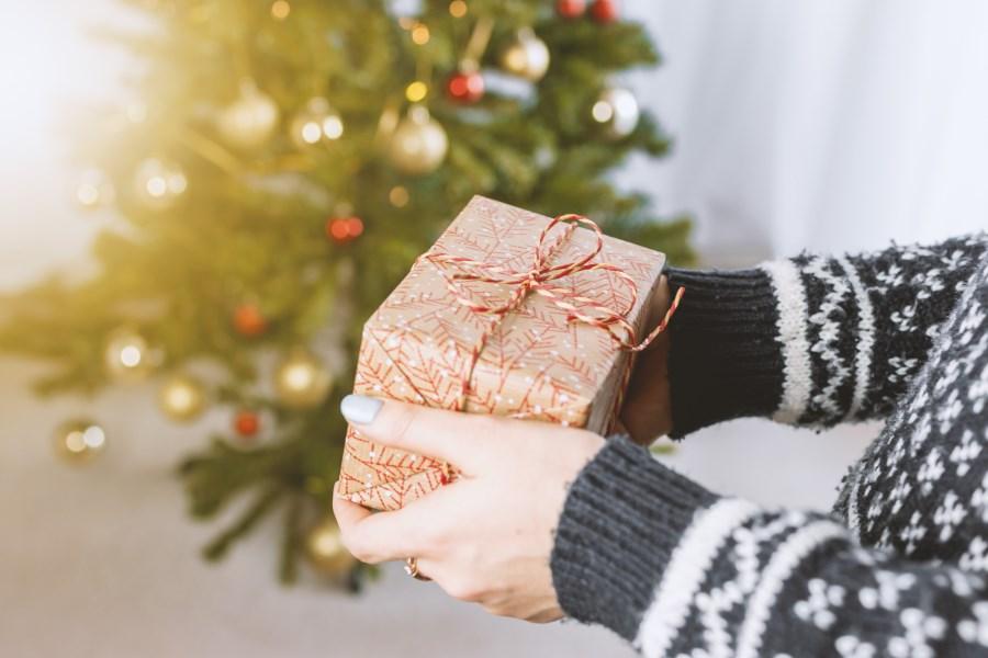 Person hält vor Christbaum ein Weihnachtsgeschenk in den Händen