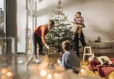 Mutter, Vater und zwei Kinder schmücken gemeinsam den Christbaum