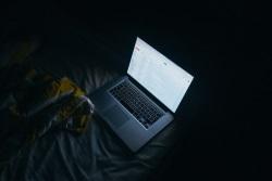 laufender Laptop im Dunkeln auf Bett