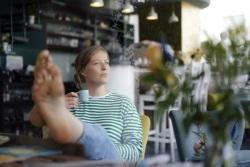 junge Frau genießt auf Terrasse Getränk