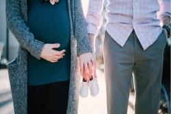 schwangere Frau und Partner halten gemeinsam Babyschuhe in den Händen