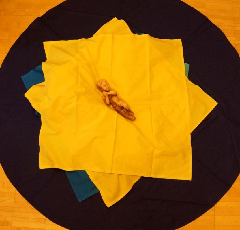 Christkindfigur in gelben Tüchern liegend