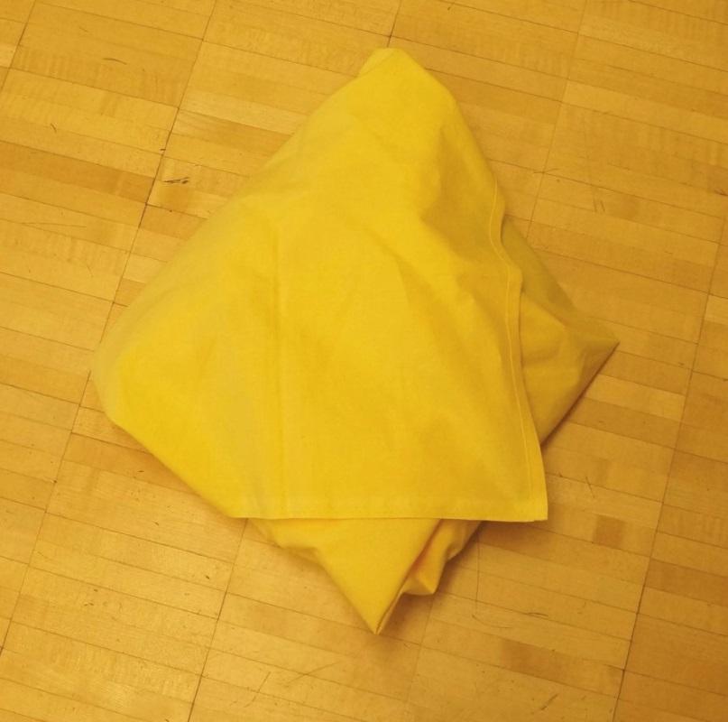 Puppe komplett in gelbe Tücher eingewickelt