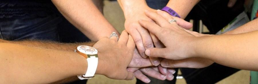 Hände legen sich übereinander