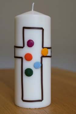 Kerze mit selbst gestaltetem Kreuz, in dem bunte Wachskugeln kleben