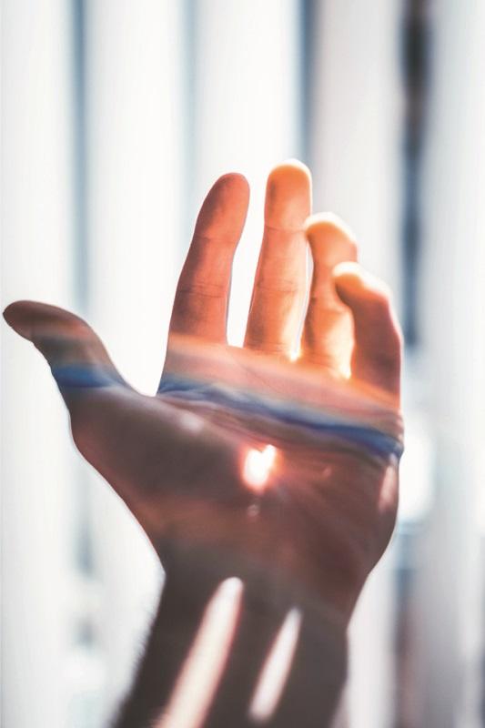 ausgestreckte Hand mit Spiel aus Licht und Schatten