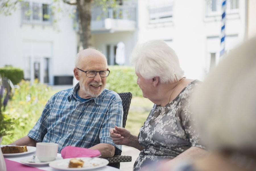 älterer Herr und ältere Dame unterhalten sich am Kaffeetisch im Garten