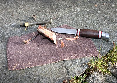Aststücke, Messer und Schmirgelpapier auf Steinboden