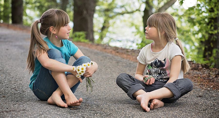 Zwei Mädchen, eins mit einem Strauß Gänseblümchen in der Hand, sitzen auf einem Weg und unterhalten sich